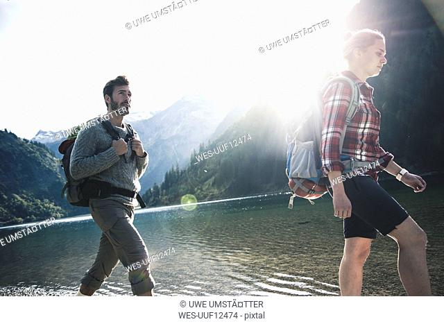 Austria, Tyrol, young couple hiking at mountain lake