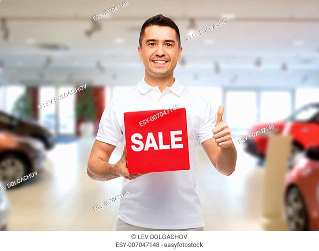 shopping, discount, consumerism, gesture and people concept - smiling man with red sale sigh showing thumbs up over auto show background