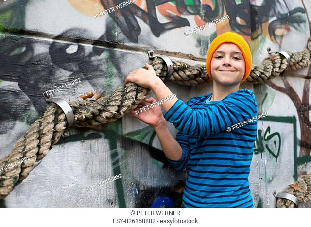young boy on a playground holding onto a rope