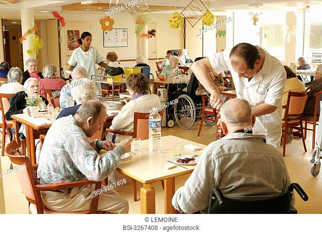 Photo essay in a Housing Institution for Dependent Elderly Persons. Two ancillary hospital staff serving the meal with residents