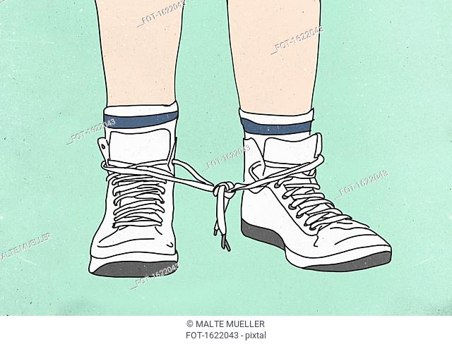 Low section of man with shoelaces tied together against colored background