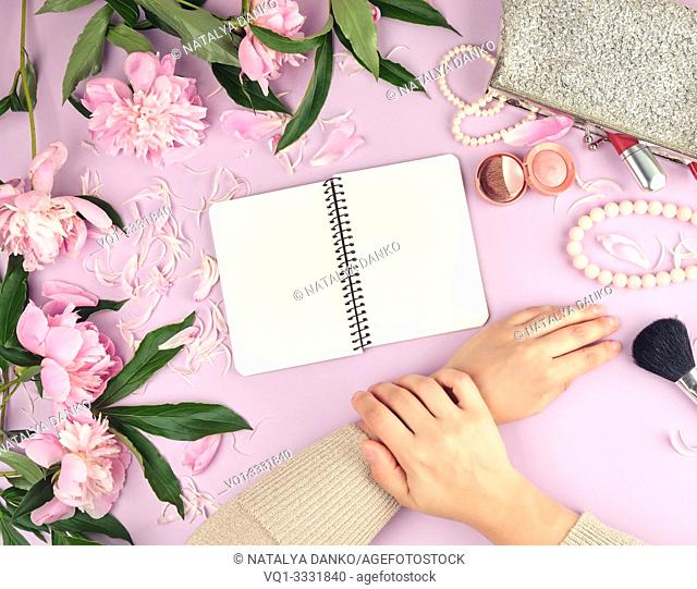 two hands with smooth skin of a young girl and a handbag with cosmetics, bouquet of blooming pink peonies, fashionable concept, top view