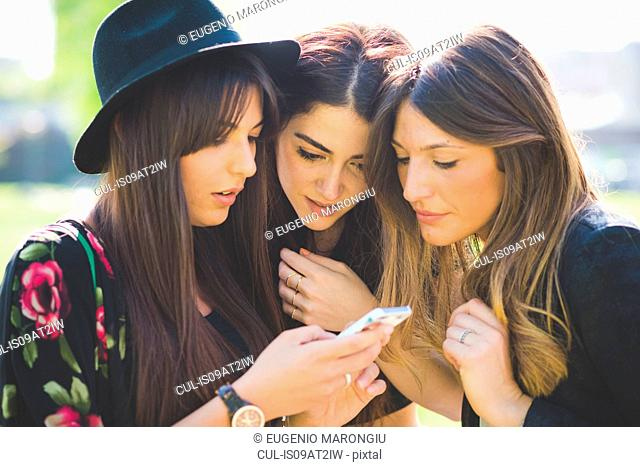 Three young female friends huddling to share smartphone text message