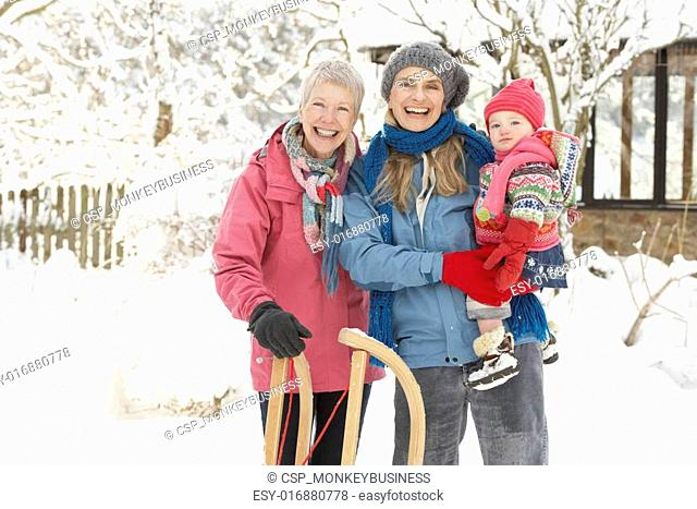 Young Girl With Grandmother And Mother Holding Sledge In Garden