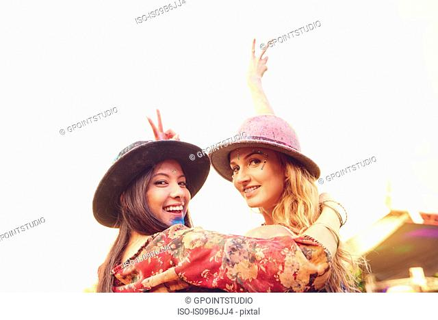 Portrait of two young female friends making peace sign at festival