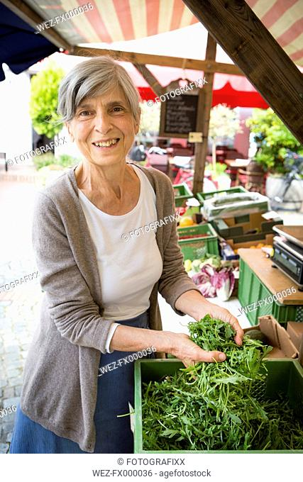 Portrait of smiling senior saleswoman with roquette at her vegetable stand