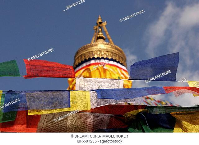 Red, yellow, white, blue and green prayer flags at the Bodnath stupa, accompanied by traditional Tibetan prayer verses Om mani padme hum