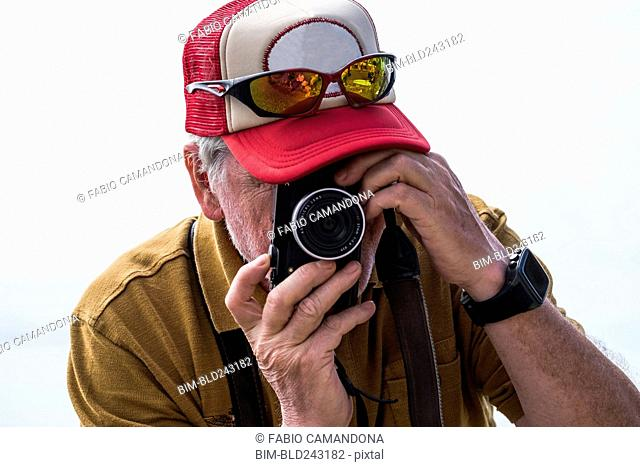 Caucasian man photographing with camera