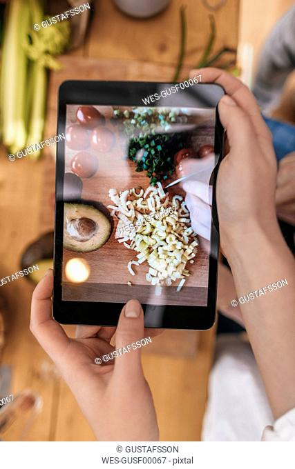 Woman taking picture of prepared vegetables with tablet, close-up