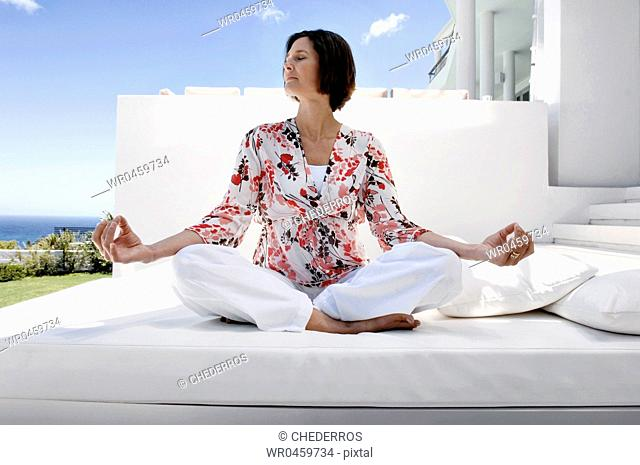 Mature woman sitting in a lotus position