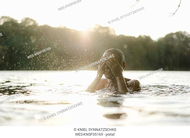 Woman in a lake at sunset splashing with water