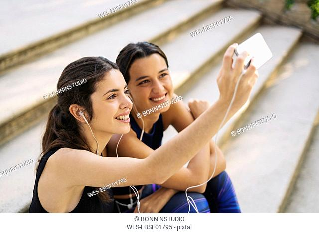 Two sportive young women sitting on stairs taking a selfie