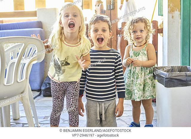 screaming infant siblings in casual clothes at home. Australian ethnicity. During holiday stay in Hersonissos, Crete, Greece
