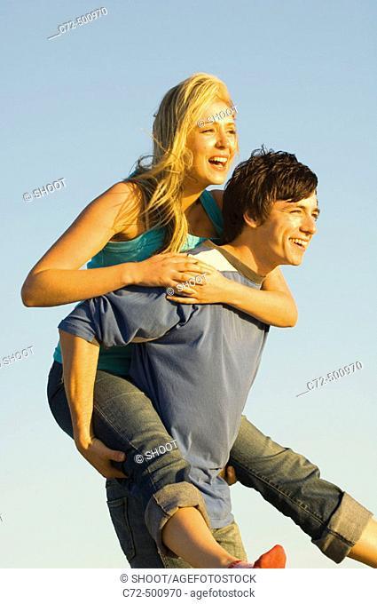 Couple having fun, piggy back riding