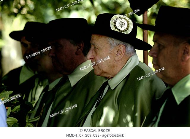 Side profile of a senior man with three mature men in a row
