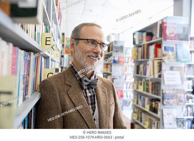 Smiling bookstore owner leaning on shelf