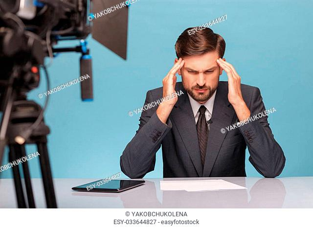 Skillful young tv reporter has a headache. He is sitting at desk in studio and touching his temples with disappointment. Focus on camera