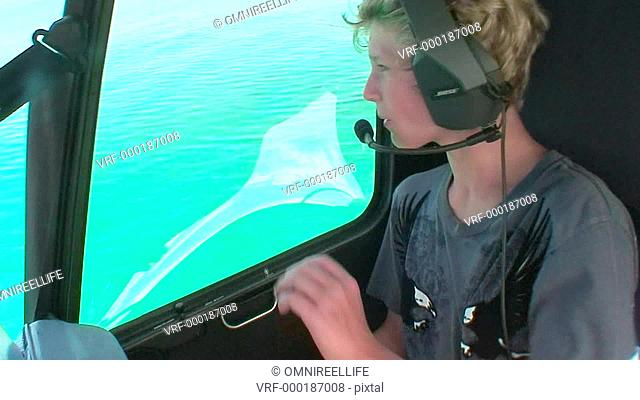 Teenage male wearing headphones and microphone waving out of helicopter window towards white boat on ocean below