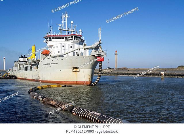 Trailing suction hopper dredger Alexander von Humboldt in port of Ostend discharging sand via long hoses / floating pipeline to beaches, Belgium