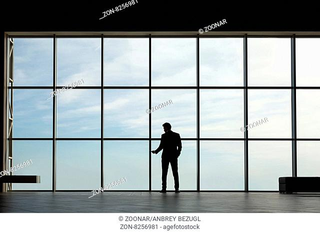 Silhouette business man in a suit in a large window to the floor. In the hands holding the phone. Horizontal photo
