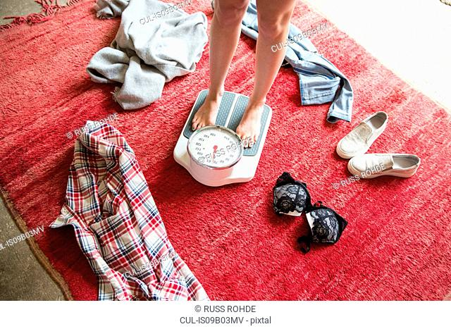 Legs of undressed young woman standing on weighing scales