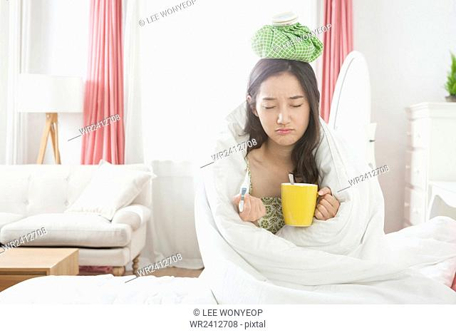 Portrait of young sick woman in blanket holding thermometer an mug with ice pack on her head