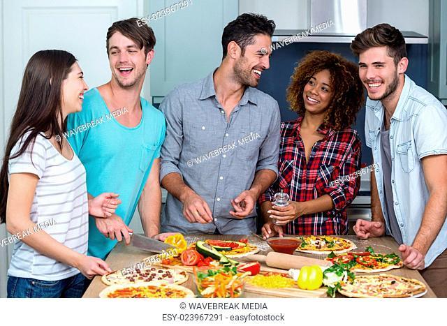 Cheerful multi-ethnic friends preparing pizza at home