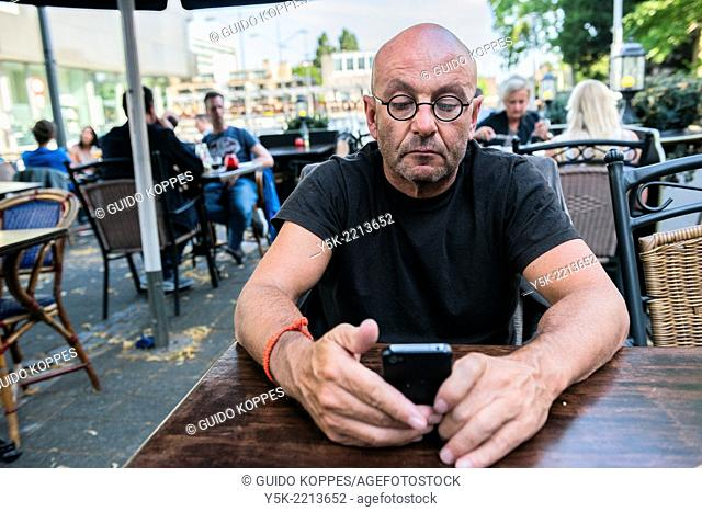 Tilburg, Netherlands. Bald, be glassed and middle-aged man, reading his iPhone messages, while sitting down at an outdoor restaurant table