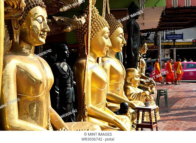 Tall golden Buddha statues lined up on a pavement