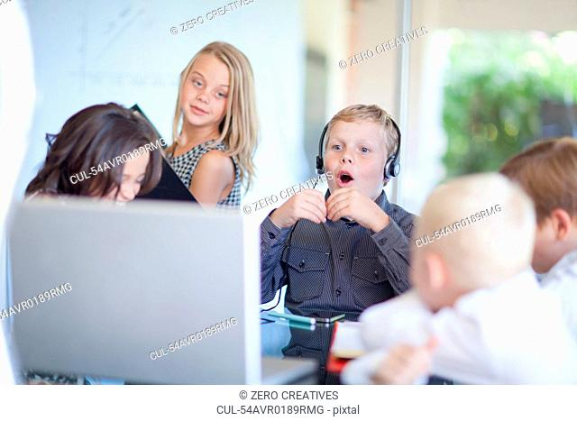 Children playing business people at desk