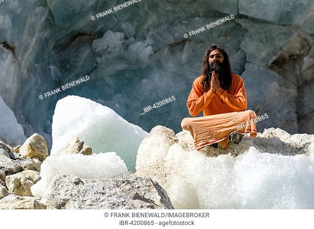 A Sadhu, holy man, is sitting and praying in lotus pose, padmasana, on a block of ice at Gaumukh, the main source of the holy river Ganges, Gangotri