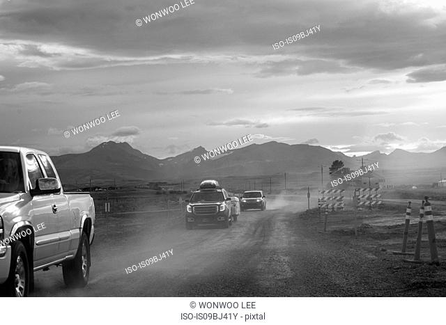 Pick-up and cars on dusty dirt track at dusk, B&W, Browning, Montana, USA