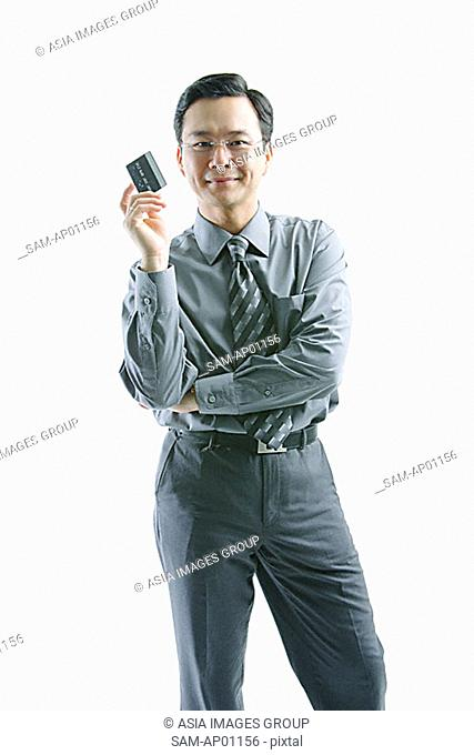 Businessman holding credit card, arms crossed, looking at camera