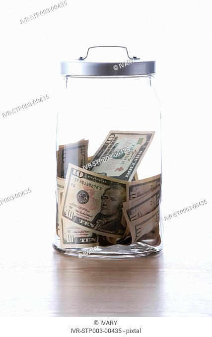 Glass jar filled with American dollar bills