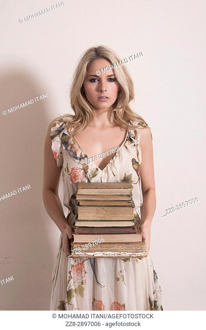 Young woman holding a pile of old books