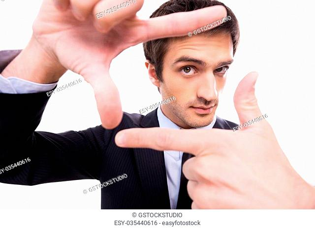 Focusing at you. Wide-angle image of young man in formalwear gesturing finger frame and looking through it while standing isolated on white background