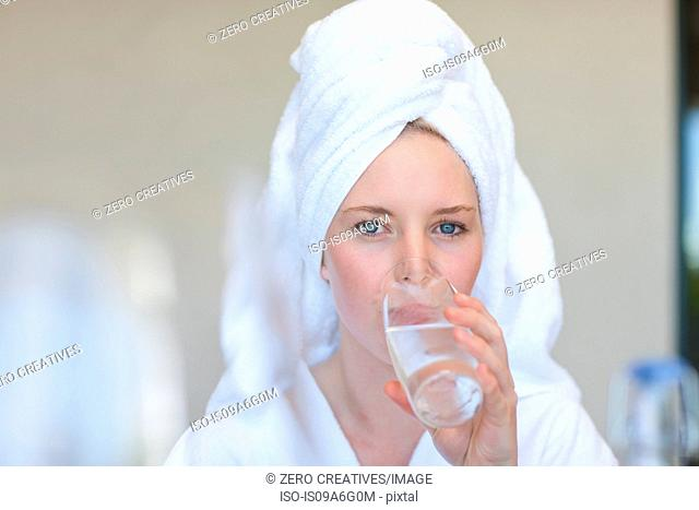 Young woman wearing towel on head drinking water