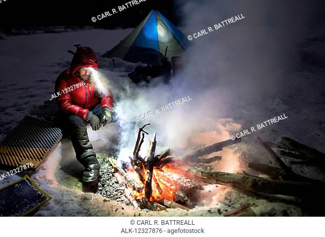 Man Cooking Over An Open Fire At Night In Winter, Denali State Park, Southcentral Alaska, USA