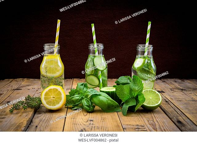 Three glass bottles of table water flavored with different fruits and herbs