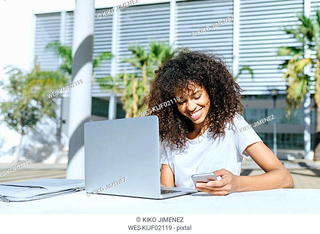 Smiling young woman with laptop sitting at table outdoors using smartphone
