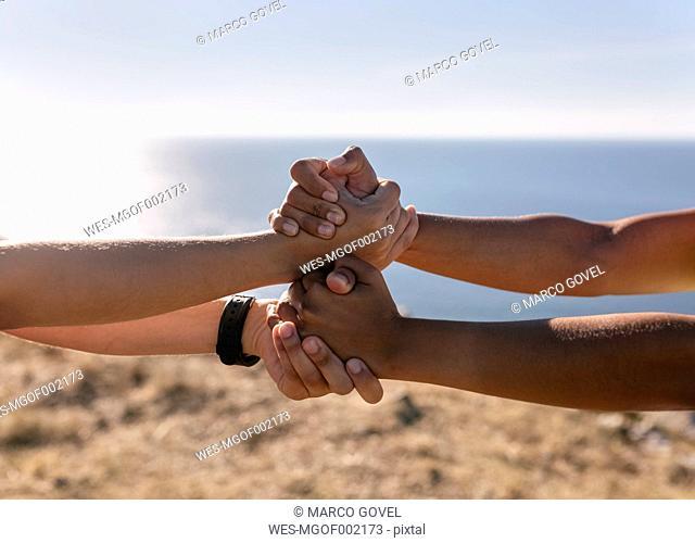Spain, Asturias, two sportswomen training on the coast, holding hands