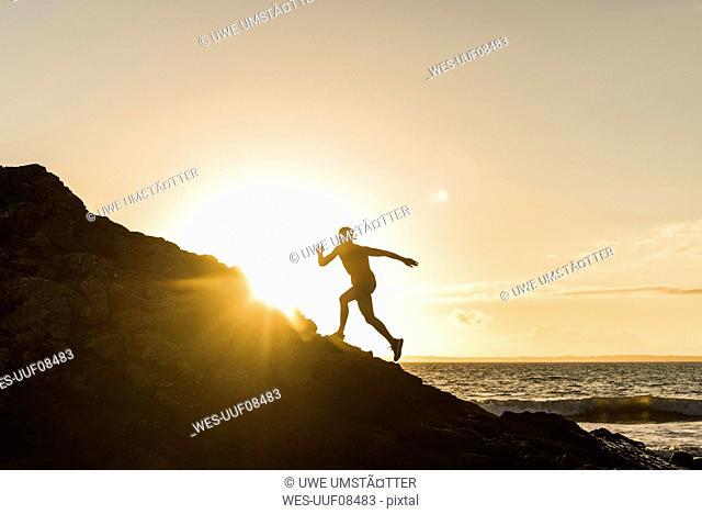 France, Crozon peninsula, jogger on rock at sunset