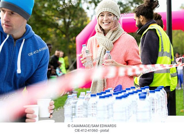 Portrait smiling female volunteer handing out water at charity run