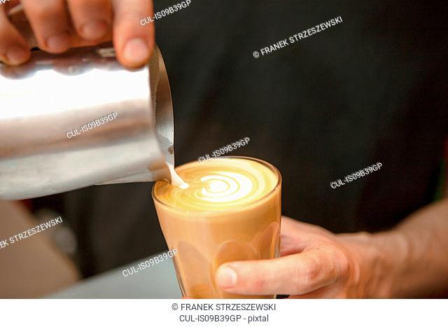 Close up of barista's hands pouring milk into coffee in cafe
