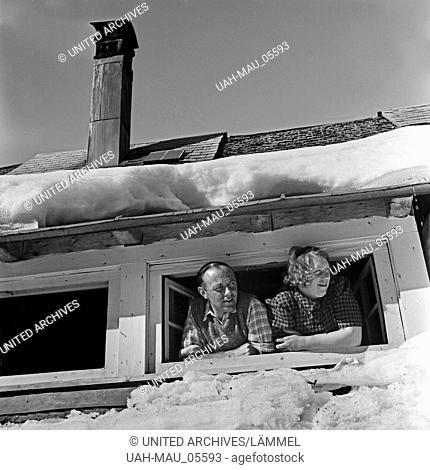 Eine Frau und ein Mann schauen aus ihrem Dachfenster, Deutschland 1930er Jahre. A man and a woman looking out of their roof window, Germany 1930s