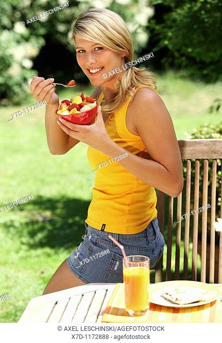 woman sitting in the garden eating fruit salad