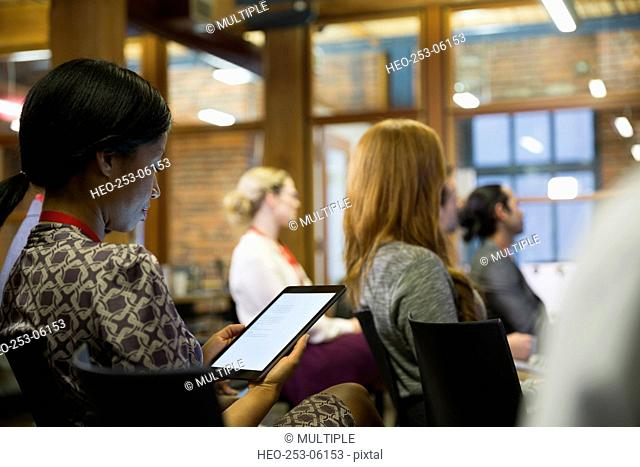 Businesswoman using digital tablet in conference audience