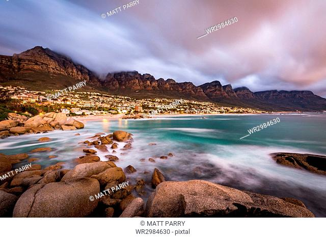 Long exposure at sunset at Camps Bay with cloud over Table Mountain and the Twelve Apostles, Cape Town, South Africa, Africa