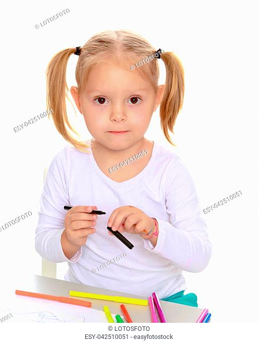 Pretty little blonde girl drawing with markers at the table.Girl holding in hands blue marker