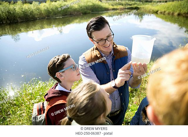 Science teacher students examining pond water field trip